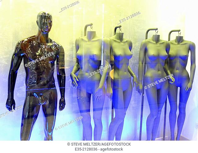 A male mannequin and four female mannequins await clothing