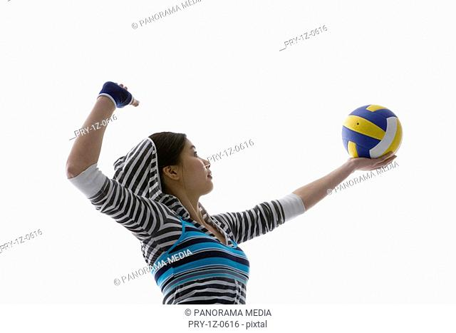 a fashionable woman with a volleyball in her hand