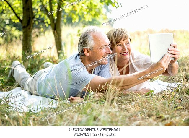 Happy senior couple lying in meadow takinhg a selfie with tablet