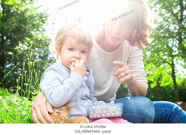 Mother and female toddler eating sweets in park