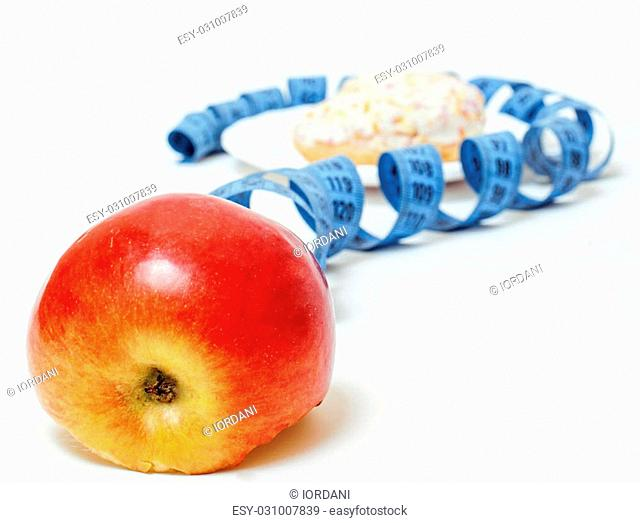 New diet concept, measurement tape in shape of question mark between red apple and doughnut on a white background