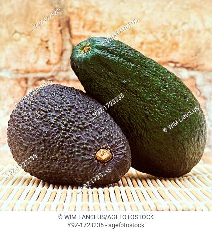 Two avocados on bamboo mat