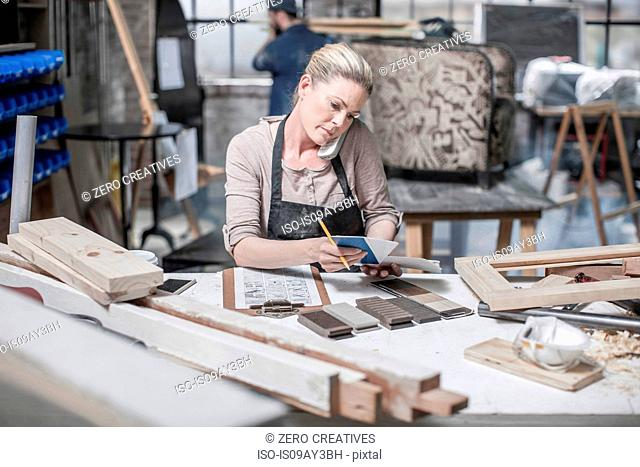 Craftswoman talking on smartphone and checking diary in antique restoration workshop