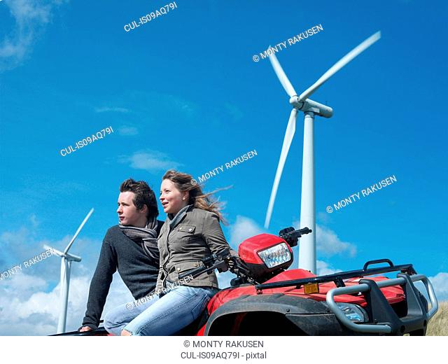 Brother and sister sitting on quadbike at windfarm