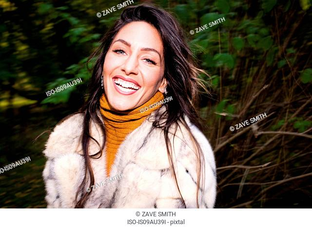 Portrait of mid adult woman wearing fur coat looking at camera smiling