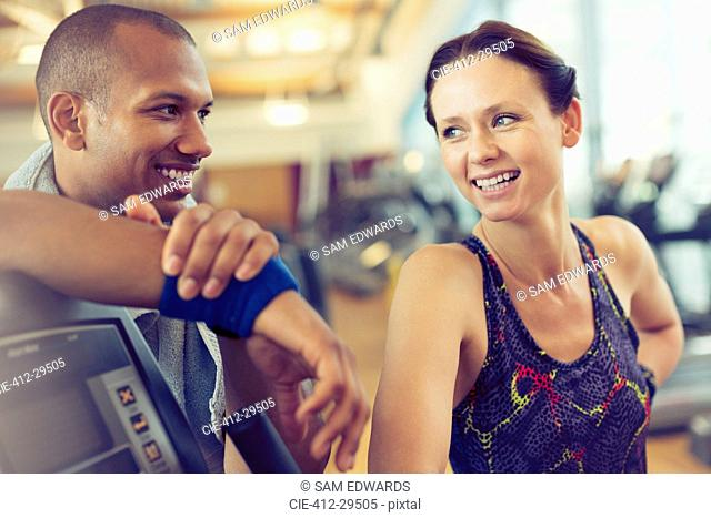 Smiling man and woman resting at gym