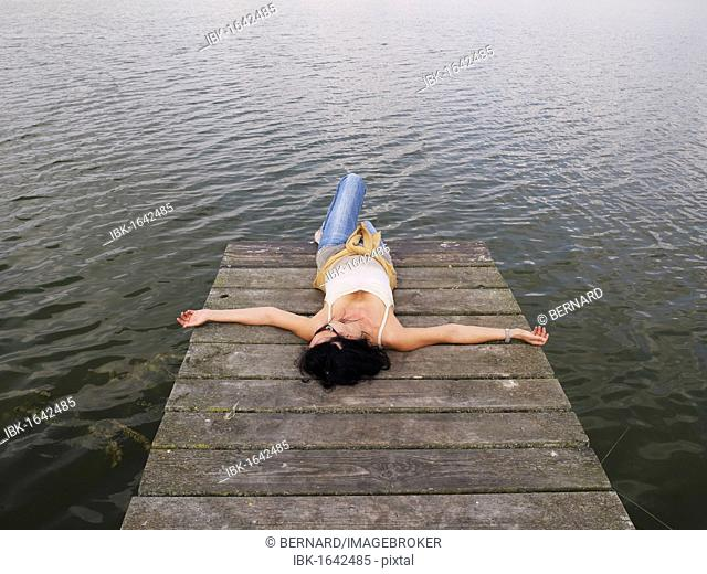 Woman relaxing lying on a wooden pier at a lake, Mecklenburg Lake District, Mecklenburg-Western Pomerania, Germany, Europe