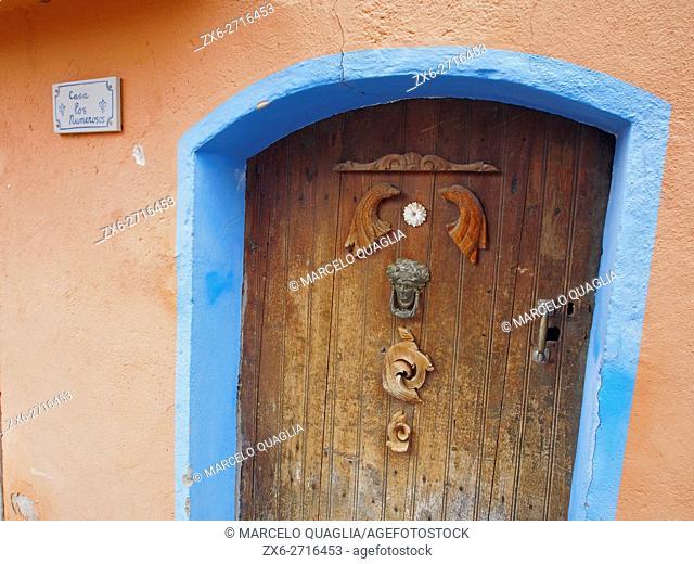 Wooden door decorated with small sculptures at Serradell hamlet of Pallars Jussaregion. Lleida province, Catalonia, Spain