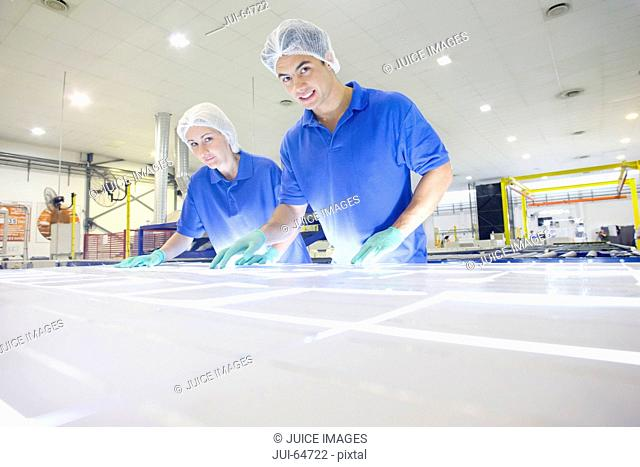 Technician worker smiling at camera arranging solar cells to form solar panel on production line