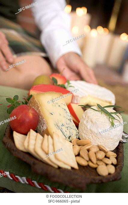 Hands serving cheeseboard with fruit and crackers