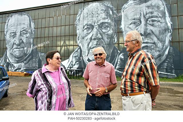 Former miners Monika Mietsch (L-R), Hans-Georg Petschke and Horst Richter stand before oversize portraits in the Ferropolis open museum in Graefenhainichen