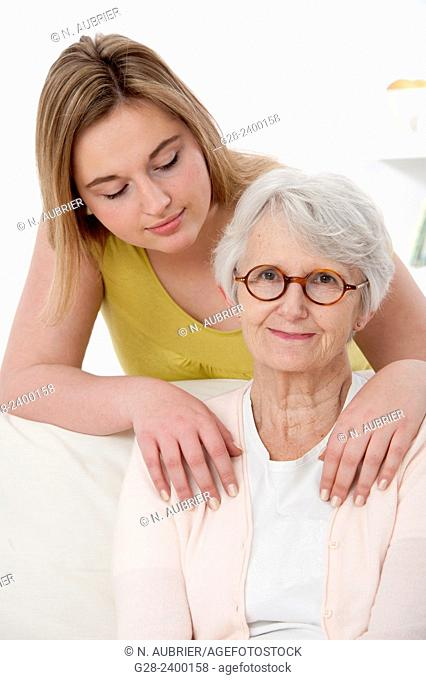 Young medical help or granddaughter holding beautiful senior woman by her shoulders, and smiling to her, at home