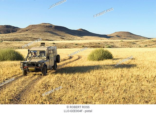 Tourist On Safari in a 4X4Vehicle  Palmwag Rhino Camp Area, Damaraland, Palmwag Concession, Namibia, Africa