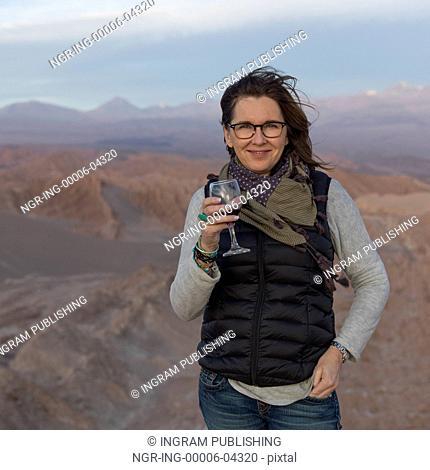 Portrait of woman holding a wine glass in desert, San Pedro de Atacama, El Loa Province, Antofagasta Region, Chile