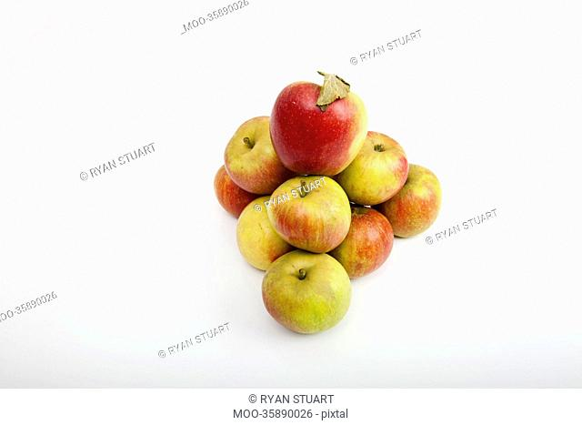 Fresh apples forming pyramid over white background