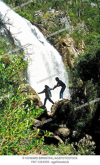 Couple seen in silhouette crossing waterfall