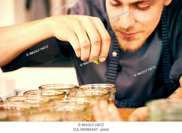 Chef seasoning food in plastic containers