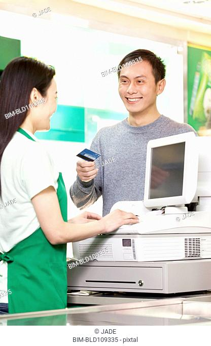 Chinese customer handing cashier credit card in grocery store