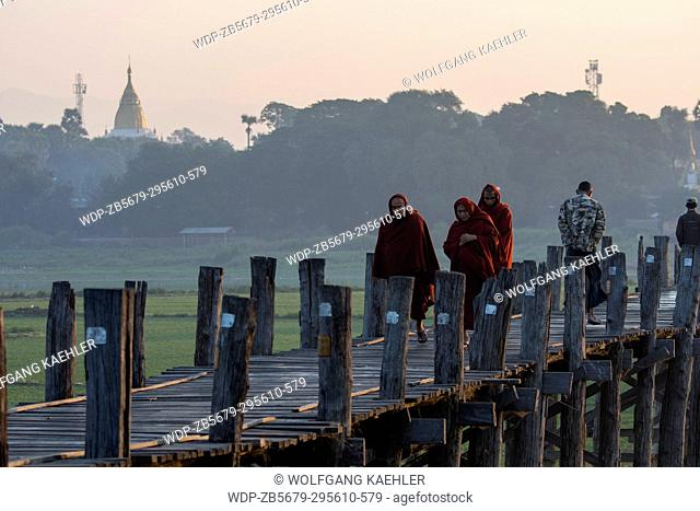 Buddhist monks are walking on U Bein Bridge (built around 1850 and is believed to be the oldest and longest teakwood bridge in the world) spanning Taungthaman...