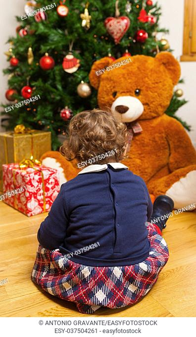 Beautiful toddler baby girl with gifts and christmas tree