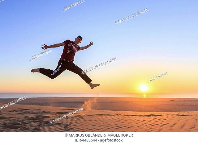 Young man jumping happily in the air, sunset, Namib desert, Langstrand, Swakopmund, Erongo Region, Namibia
