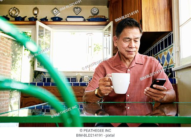 Filipino man using cell phone in kitchen
