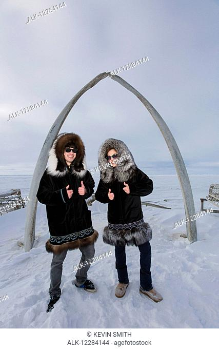 Male and female native youths wear traditional fur parkas while standing next to the Browerville Walebone arch, Barrow, North Slope, Arctic Alaska, USA, Winter