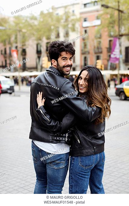 Spain, Barcelona, young couple embracing and walking in the city