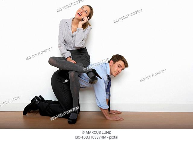 Business woman sitting on man's back