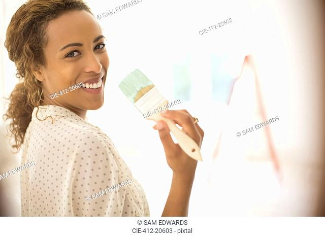 Woman holding paint brush in living space