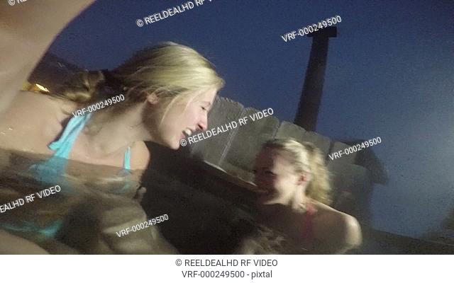 Young women enjoying steam water in hot tub during winter