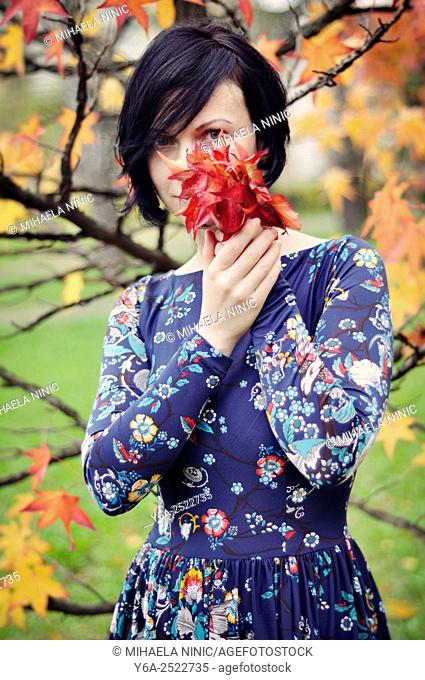 Woman holding leaves close to her face, autumn