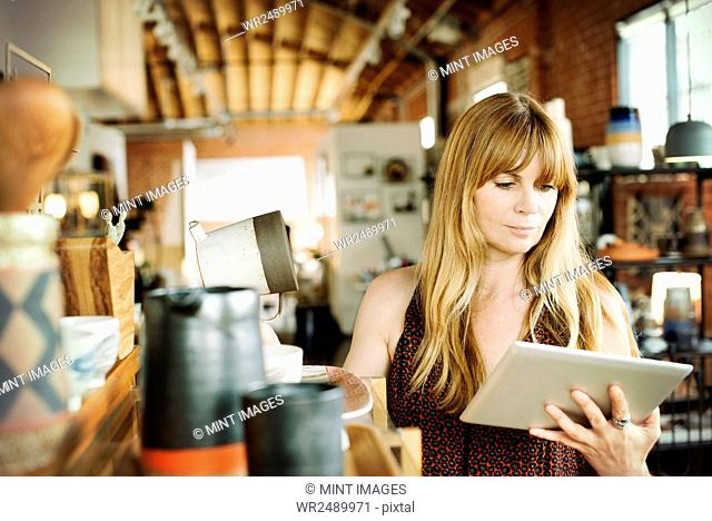 Woman in a shop, holding a digital tablet and ceramic jug