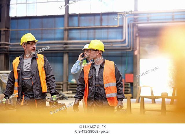 Male workers walking in factory