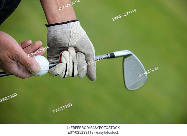 Golf club and ball in hand, France