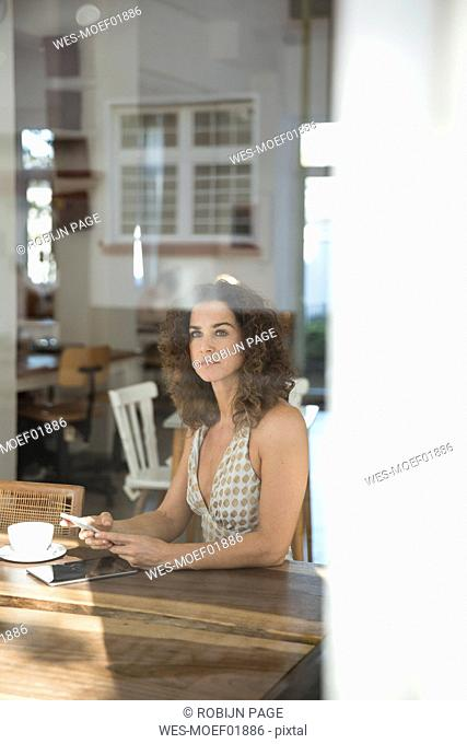 Mature woman sitting in coffee shop with smartphone and digital tablet