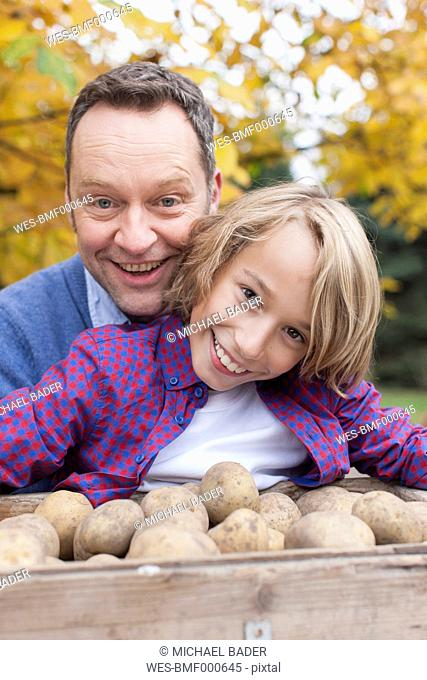 Germany, Leipzig, Father and son collecting potatoes