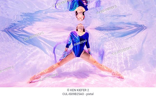 Underwater view of girl wearing blue leotard and ballet shoes, facing surface of water