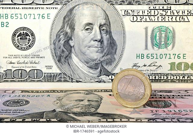 Euro coin on U.S. dollar banknotes, symbolic image for exchange rates