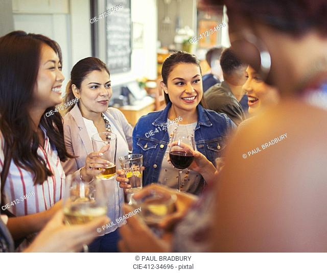 Women friends talking and drinking beer and wine at bar