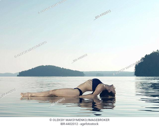 Young woman practicing yoga on a platform in water on the lake during misty morning light, Yoga Fish posture, Matsyasana