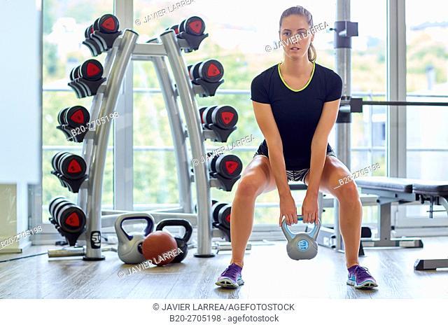 Kettlebells, Woman lifting weights at the gym