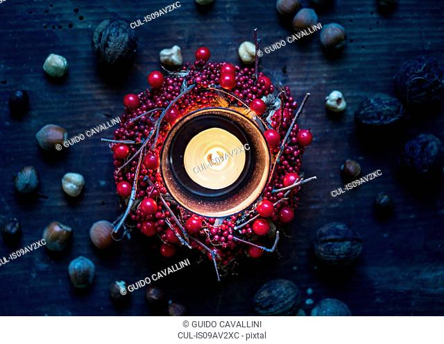 Overhead view of burning candle surrounded by berry wreath and nuts