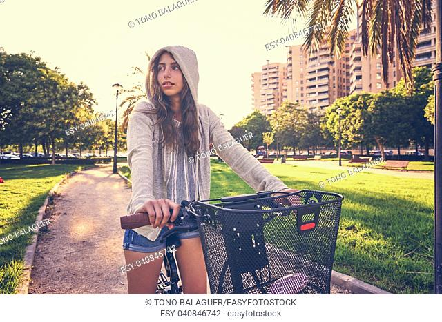 Brunette girl riding bike in the park with hoodie sweater