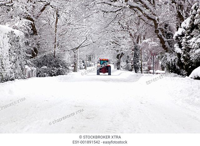 A red tractor driving down a snow covered UK road during the winter snowfall winter in January 2010