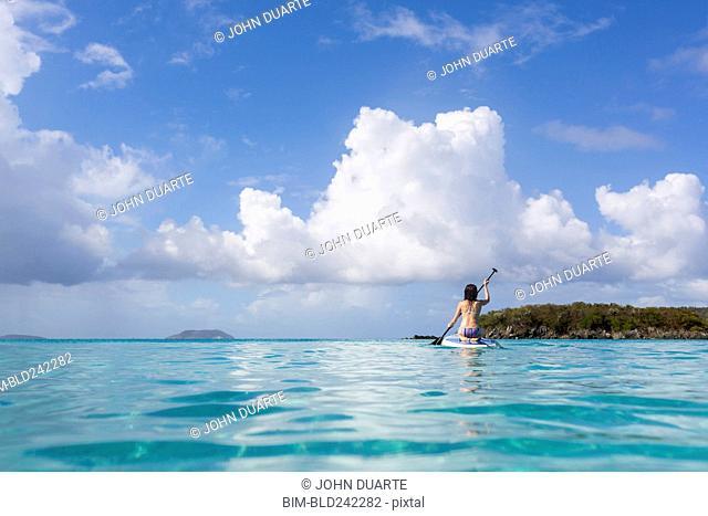Caucasian woman paddling surfboard on tropical ocean