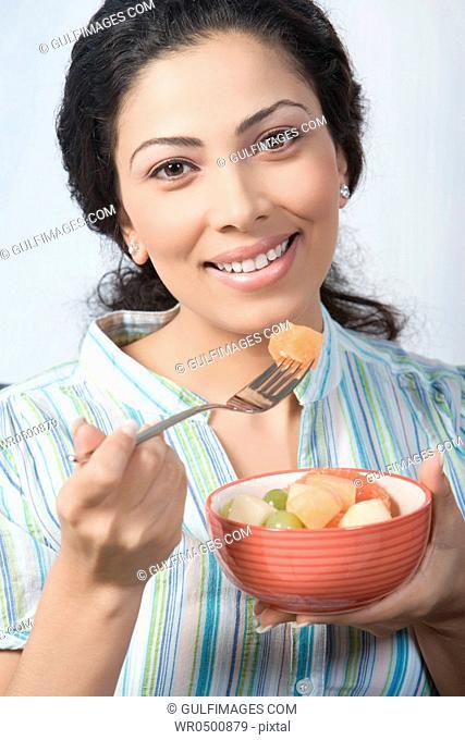Young woman holding fruit salad, portrait