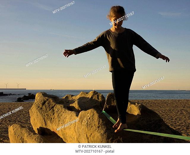 Girl balancing along a slackline on a beach in Northern Spain