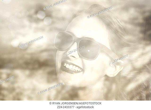 Vintage filtered photo of a young pin-up woman looking through car window while travelling through a countryside forest. Memories in reflection