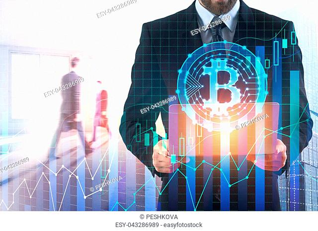 Businessman using laptop with bitcoin hologram in abstract blurry office interior. Money and trade concept. Double exposure